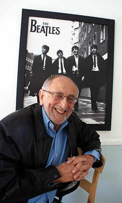 Ivor Davis, as he appears today, poses before a 1964 poster of The Beatles